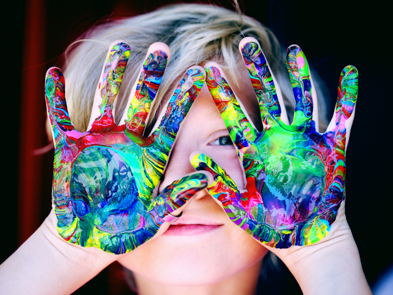 A young boy with painted hands